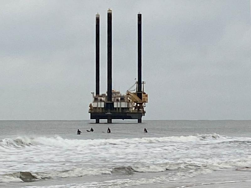 Surfers near Georgica Beach dwarfed by an exploratory driling rig taking sea-floor samples in preparation for a planned electric cable installation